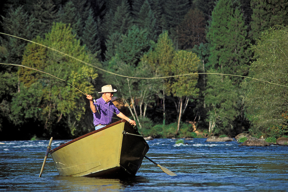 Angler fly fishing from a drift boat on the McKenzie River; Cascade Mountains, Lane County, Oregon.