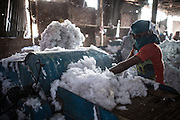 The air of a recycled cotton factory is thick with dust. Workers wear little for protection.