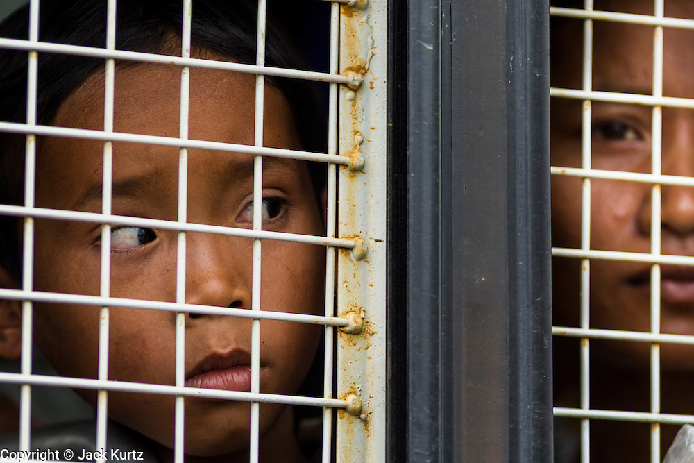 16 JUNE 2014 - POIPET, CAMBODIA: Cambodian women locked in a Thai immigration police truck arrive in Poipet, Cambodia. More than 150,000 Cambodian migrant workers and their families have left Thailand since June 12. The exodus started when rumors circulated in the Cambodian migrant community that the Thai junta was going to crack down on undocumented workers. About 40,000 Cambodians were expected to return to Cambodia today. The mass exodus has stressed resources on both sides of the Thai/Cambodian border. The Cambodian town of Poipet has been over run with returning migrants. On the Thai side, in Aranyaprathet, the bus and train station has been flooded with Cambodians taking all of their possessions back to Cambodia.  PHOTO BY JACK KURTZ