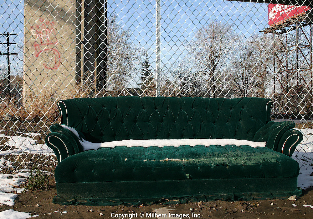 A Victorian style green couch which sits below a freeway bridge with Red Wings billboard ad in the distance.