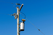 Electricity transformer, power lines and insulators on a wooden power pole. <br />
