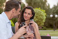 Romantic young couple holding hands while having red wine in park