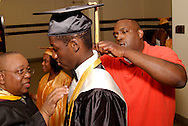 Salutatorian Celestine John Wenegieme (center) is attended to by music and band teacher Mr. Fedrick (left) and paraproffesional Russell Bass before the Fiftieth Meadowdale High School commencement at the Dayton Masonic Center, Saturday, May 21, 2011.