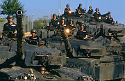 Arranged on a hill with their barrels pointing upwards and lights glowing, weathered Challenger 1 tank crews of the 1st Batallion Royal Tank Regiment are stationary at Tidworth Barracks, England. Their turrets are all pointing to the viewer and the helmet heads of their commanders and drivers can be seen  protruding from their respective places. The Royal Tank Regiment is an armoured regiment of the British Army but tanks were first used at Flers in September 1916 during the Battle of the Somme in World War I. Challenger 1 was the main battle tank (MBT) of the British Army from 1983 until superseded by the Challenger 2 in the mid 1990s. Challenger 1 took part in Operation Desert Storm where the Iraqi forces failed to take a single vehicle out of combat while Challenger destroyed roughly 300 Iraqi tanks.