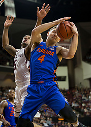 Florida guard Egor Koulechov (4) pulls down a rebound against Texas A&M guard Savion Flagg (5) during the first half of an NCAA college basketball game Tuesday, Jan. 2, 2018, in College Station, Texas. (AP Photo/Sam Craft)