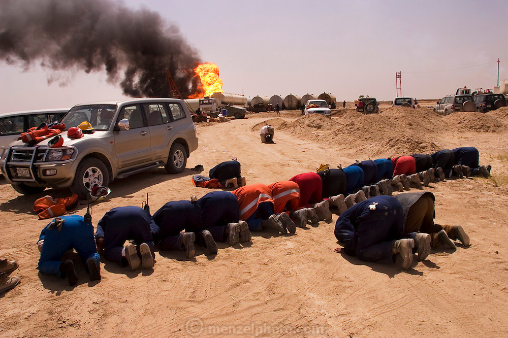 Firefighters from the Kuwait Oil Company (called KWWK: Kuwait Wild Well Killers) pray at noon by the second oil well fire they were working on in Iraq's Rumaila Oil field. The Rumaila field is one of Iraq's biggest oil fields with 5 billion barrels in reserve. Many of the wells are 10,000 feet deep and produce huge volumes of oil and gas under tremendous pressure, which makes capping them very difficult and dangerous. Rumaila is also spelled Rumeilah.
