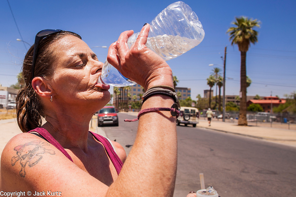 "20 JUNE 2012, PHOENIX, AZ:   A homeless woman drinks from a bottle of water in Phoenix, AZ, Wednesday. June 20 is the first day of summer in the northern hemisphere. The high temperature in Phoenix Wednesday soared to over 110 (F), well above the normal of 105. The hot weather is especially stressful on the homeless, who don't have the opportunity to get into air conditioning or access to cold water. ""I Will Listen,"" an outreach organization that assists the homeless and community of street people in Phoenix, AZ, provides free food and cold drinks to the homeless in central Phoenix. They ran out of drinks and food in about one hour during Wednesday's outreach.       PHOTO BY JACK KURTZ"