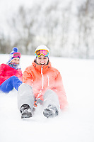 Young woman enjoying sled ride in snow with friend in background