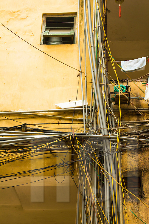 """Bunch of messy PVC plumbing and electric wires hooked on a yellow wall in a """" khu thap the"""" (KTT) building, an architecture style housing famous in Vietnam. Hanoi, Vietnam, Asia."""