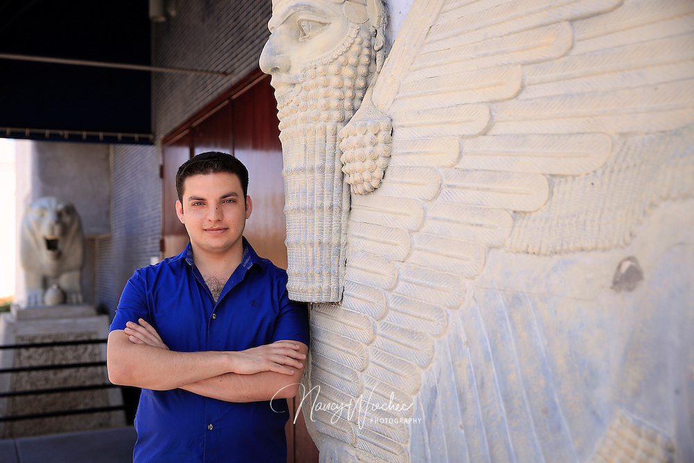 Chaldean Iraqi refugee Martin Banni, 24, stands between symbols of ancient Babylon -- a lion and lamassu -- outside the parish hall at St. Peter Chaldean Catholic Cathedral in El Cajon, Calif., Aug. 15, 2015. Banni and his pastor were the last two people to leave the village of Karamles before ISIS took over. (Nancy Wiechec for ONE magazine)