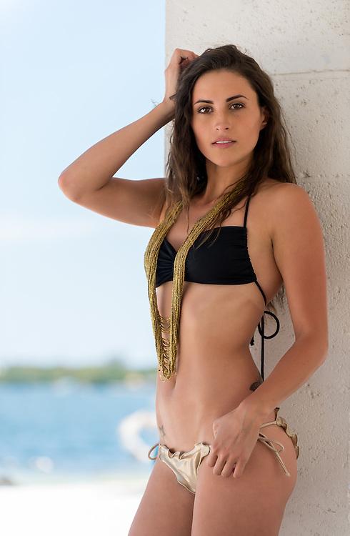Sexy Latin woman posing with her seductive bikini in a tropical beach