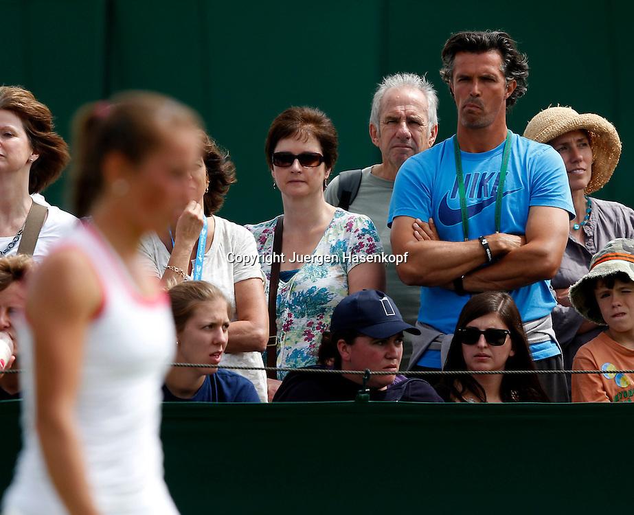 Wimbledon Championships 2012 AELTC,London,.ITF Grand Slam Tennis Tournament,.Robert Orlik,Trainer von Annika Beck (GER) steht zwischen den Zuschauern und schaut skeptisch,Spielerin unscharf im Vordergrund,Querformat,coach,.