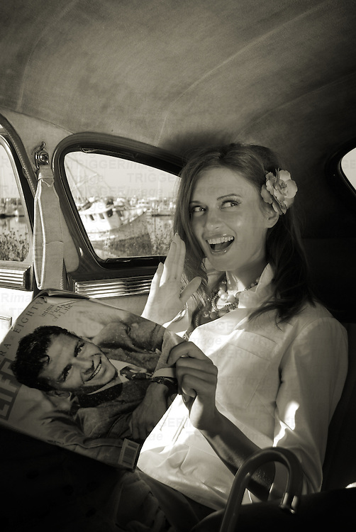 A model looking at a magazine sitting in a car