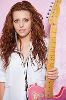 Portrait of stylish teenage girl holding guitar