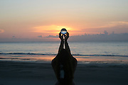 red head woman holding crystal ball at sunrise on Jekyll Island beach