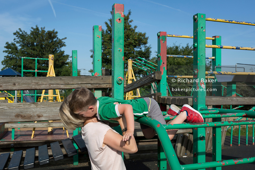 A mother rescues her child from the height of a playpark climbing frame, on 25th August, in Ruskin Park, London borough of Lambeth, England.