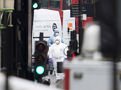 © Licensed to London News Pictures. 04/06/2017. London, UK. Policeman in protective suits are seen next to a van believed to have been driven by the attackers - after an attack by three men killed seven and injured at least 48. Police shot three attackers dead after they deliberately drove their van at people on London Bridge and then stabbed drinkers at bars in nearby Borough Market. Photo credit: Peter Macdiarmid/LNP