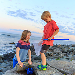 A girl and her brother play on the rocks at Seapoint Beach in Kittery, Maine.