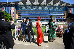 © Licensed to London News Pictures. 21/06/2018. London, UK. Racegoers those for photographs at Ladies Day at Royal Ascot at Ascot racecourse in Berkshire, on June 21, 2018. The 5 day showcase event, which is one of the highlights of the racing calendar, has been held at the famous Berkshire course since 1711 and tradition is a hallmark of the meeting. Top hats and tails remain compulsory in parts of the course. Photo credit: Ben Cawthra/LNP