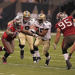 2008 September 7: Running back Reggie Bush (25) of the New Orleans Saints runs between Tampa Bay Buccaneers defenders Jovan Haye (71) and Chris Hovan (95) during the first half of their game at the Louisiana Superdome in New Orleans, LA.