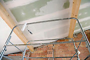 paint roller hanging from a platform looking up to a halve painted ceiling