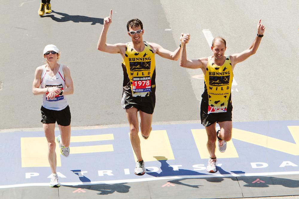 runners cross finish line at Boston Marathon