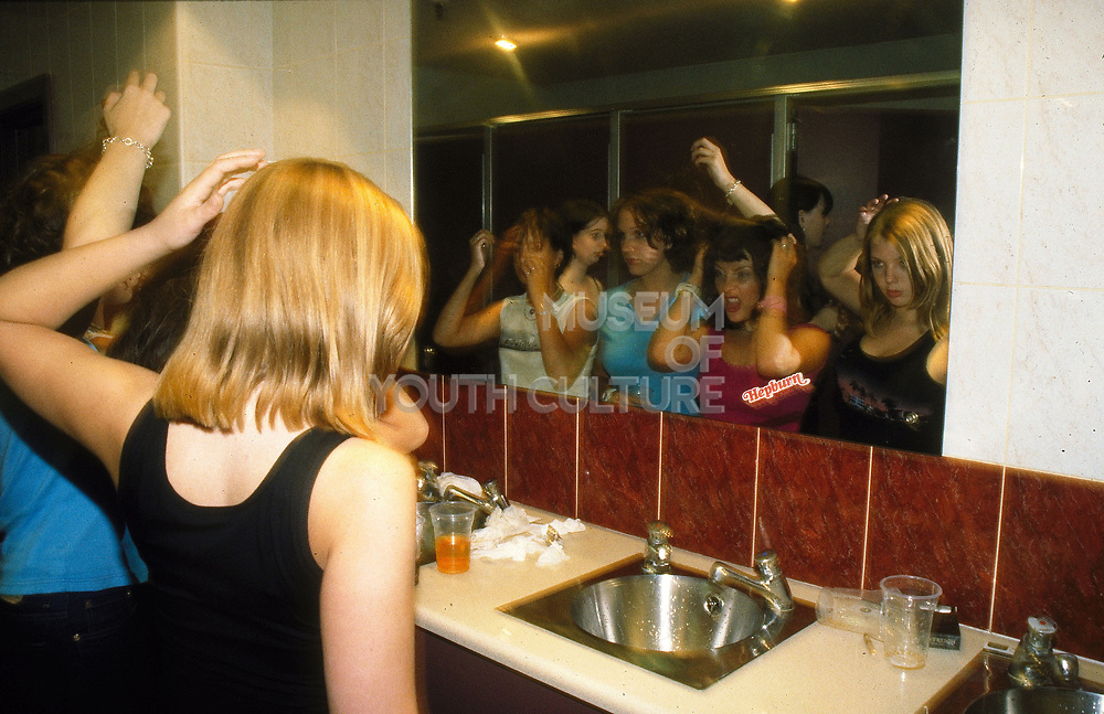 Girls checking themselves out in the toilet of a bar / club, UK, 2000's