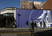 Cambridge, MA 020812  Bundledup pedestrians walk in front of a mural on Church St in Harvard Square on February 8, 2012. (Essdras M Suarez/ Globe Staff)/ MET