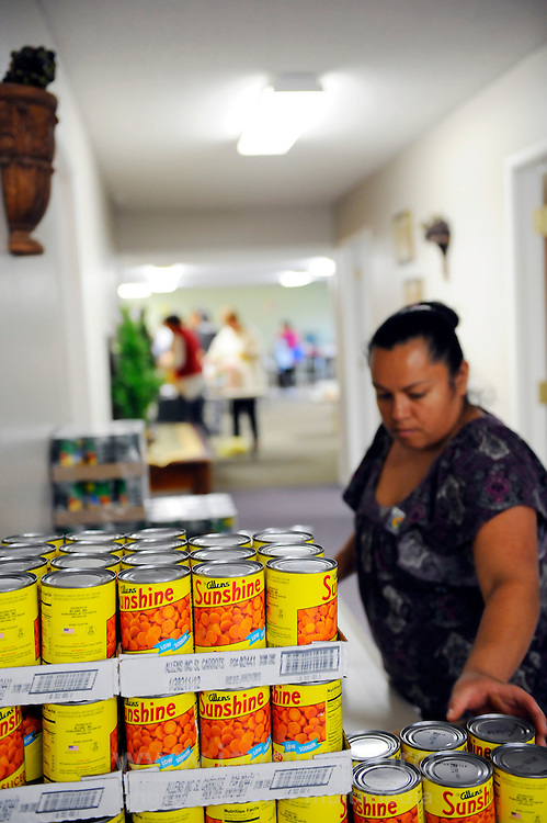 A volunteer packs canned goods at at the Vineyard Church, which runs a bi-monthly food distribution program in collaboration with the Food Bank of Monterey County.