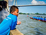 29 OCTOBER 2018 - PHRA PRADAENG, SAMUT PRAKAN, THAILAND: A boy watches a long boat go upriver towards the starting line before the long boat races in Phra Pradaeng. The longboat races go about one kilometer down the Chao Phraya River to the main pier in Phra Pradaeng. The boats are crewed by about 20 oarsmen. Longboat racing traditionally marks the end of the Buddhist Rains Retreat (called Buddhist Lent) in Thai riverside communities.       PHOTO BY JACK KURTZ