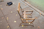broken chair and folded umbrella on pavement with autumn leaves
