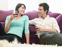 Young couple relaxing on sofa drinking wine