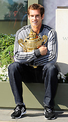 Andy Murray of Great Britain poses with the Gentlemen's Singles Trophy next to the Fred Perry statue at Wimbledon <br /> London, United Kingdom, <br /> Monday July 08, 2013. <br /> Photo by: i-Images