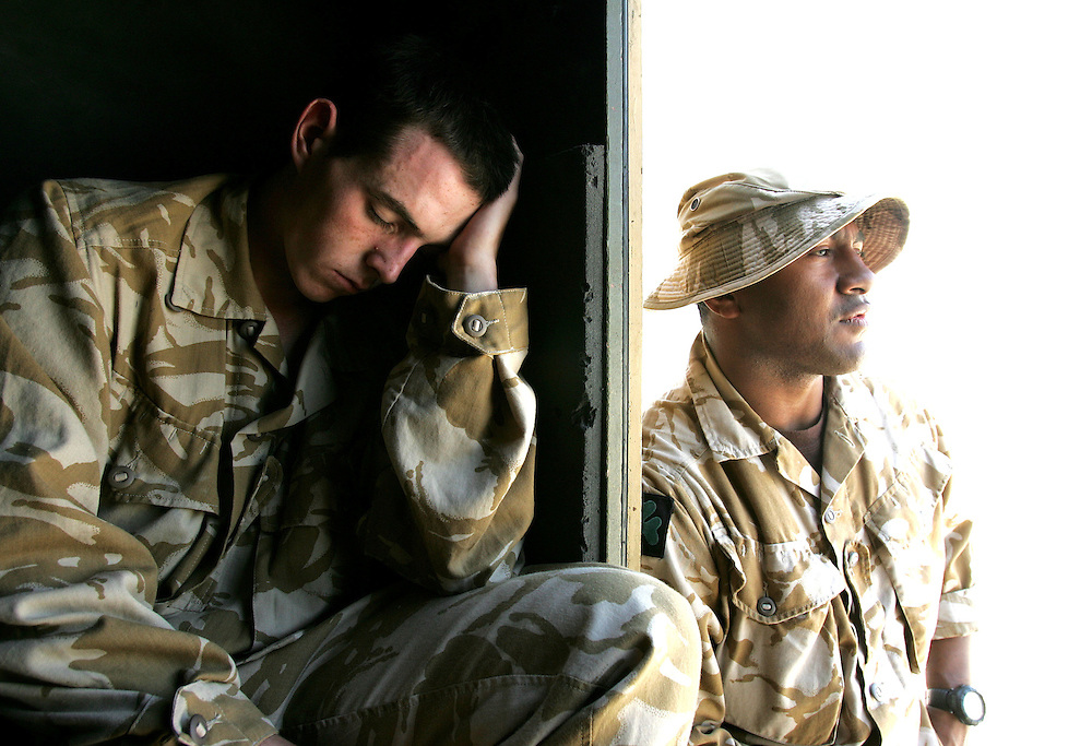 Baghdad, Iraq, 2 Oct 2005. Running 'Route Irish'...Ranger Lois Bradley (left) falls asleep exhausted on arriving at Baghdad airport. Ranger Rokodinono is at right...B Company, 1st Battalion, The Royal Irish Regiment, a tight-knit multi national fighting force make daily escorting runs along ?Route Irish?, the infamous Baghdad Airport road. The 46 man team are all British Army regulars but come from as far afield as Fiji, South Africa and Northern and Southern Ireland. Previous deployments in Kosovo, Sierra Leone and Northern Ireland have equipped them with the valuable skills needed to provide protection for British Forces and materials transiting the world?s most dangerous highway. Due to an increased presence of US forces along the route both in dug in positions and mobile patrols, attacks along the road have slackened, despite this a day rarely passed without an IED (improvised explosive device) being detonated or a small arms attack against coalition forces. ..The convoy attempts to maintain a seclusion ?bubble? around its vehicles for the duration of the journey. Any civilian vehicle that either strays into the bubble or refuses to keep their distance represents a threat and should they ignore the warning blasts on air horns carried in each vehicle the rules of engagement progress from warning shots to use of lethal force. The relative safety of the International Zone offers them an opportunity to decompress between missions. A duty driver ferries soldiers to the ?Liberty Pool?. Once only frequented by Iraq?s Ba?athist elite the luxury swimming pool and gym now fills with troops. Their body armour, helmets and weapons all within easy reach they either soak up the sun or compete with each other in diving competitions. After a daily briefing the troops have access to the ?Mosquito and Camel? bar where they watch TV or play pool and in accordance with the ?2 can rule? are allowed to drink 2 beers per night.