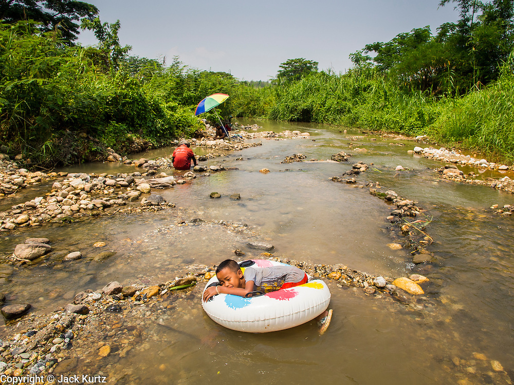 """22 APRIL 2014 - WANG NUA, LAMPANG, THAILAND: A boy in an inflatable toy floats down the Mae Wang while his parents and other villagers pan for gold. The rock lines form the outline of their claims.  Villagers in the Wang Nua district of Lampang province found gold in the Mae Wang (Wang River) in 2011 after excavation crews dug out sand for a construction project. A subsequent Thai government survey of the river showed """"a fair amount of gold ore,"""" but not enough gold to justify commercial mining. Now every year when the river level drops farmers from the district come to the river to pan for gold. Some have been able to add to their family income by 2,000 to 3,000 Baht (about $65 to $100 US) every month. The gold miners work the river bed starting in mid-February and finish up  by mid-May depending on the weather. They stop panning when the river level rises from the rains. This year the Thai government is predicting a serious drought which may allow miners to work longer into the summer.    PHOTO BY JACK KURTZ"""