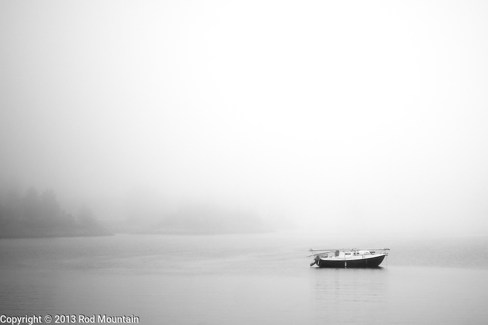 A boat sits calmly off shore on a foggy day. Vancouver, BC. Photo: © Rod Mountain