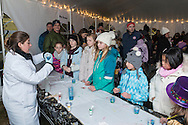 Goshen, New York - Children take part in a Mad Science activity inside a tent at the Illuminate Goshen New Year's Eve Ball Drop on Dec. 31, 2016.