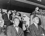 Elijah Muhammad (1897-1975, born Elijah Poole). Converted to Islam in 1931, from 1934 until his death be was leader of the Nation of  Islam. Here in 1964 addressing followers including Cassius Clay (Muhammad Ali).
