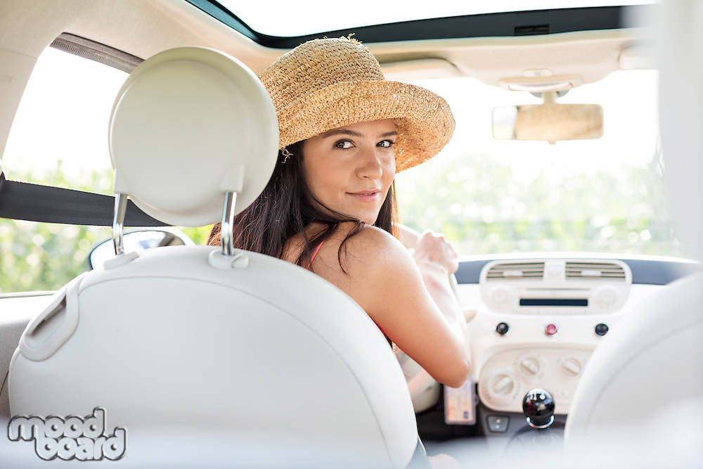 Beautiful woman looking back while driving car