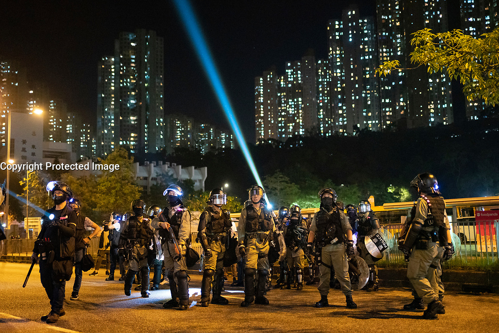 Hong Kong, China. 9th October 2019. Large peaceful crowd gathered to sing songs at MOStown mall in Ma On Shan in solidarity with several security guards who were arrested by police this week. Later small group of protestors went to nearby Shatin Divisional Police Station and shouted abuse at the police and threw objects. Riot police later charged but no arrests made. Police shine lights towards protestors after failing to make arrests after charge.  Iain Masterton/Alamy Live News.