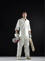 Cricket player standing holding cricket bat low angle view