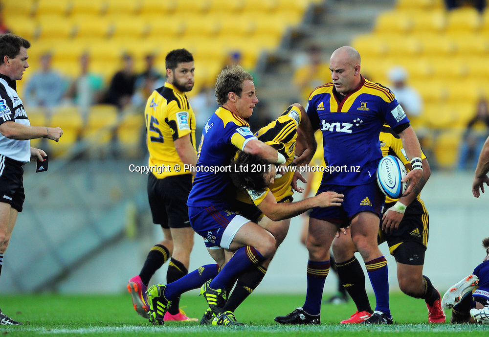 Highlanders halfback Jimmy Cowan takes out Conrad Smith off the ball as referee Stuart Dickinson (left) and Jason Rutledge (right) look on. Super 15 rugby match - Hurricanes v Highlanders at Westpac Stadium, Wellington, New Zealand on Friday, 18 February 2011. Photo: Dave Lintott/PHOTOSPORT