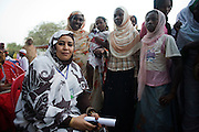 Amira Elfadil, Secretary General of the National Council of Child Welfare with local Darfuri women gathered outside the compound walls belonging to the Govenor of North Darfur in Al Fasher (also spelled, Al-Fashir) where the women from remote parts of Sudan gathered to discuss peace and political issues and celebrate Darfurian culture..
