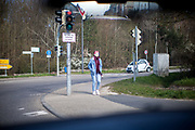 A young woman is listening to music and wearing a face mask in Oberursel im Taunus close to Frankfurt am Main.