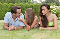 Angry young woman looking at loving couple at park