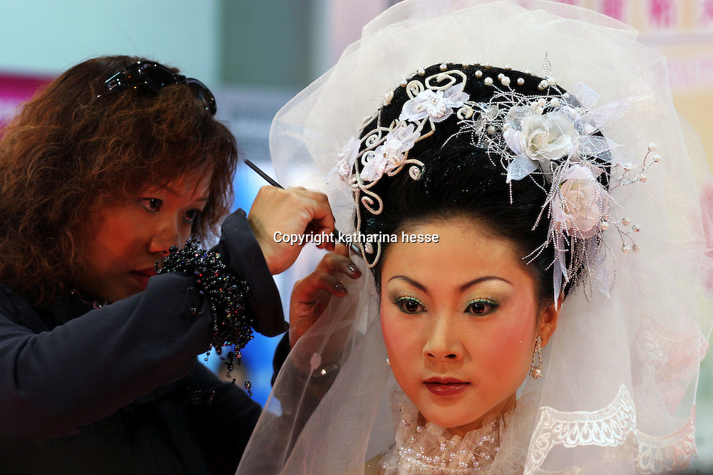 BEIJING, 22. October 2004 :a make-up artist adds final touches to a model who shows Western-style bridal wear at the International Beauty Week in Beijing, October 22, 2004, in China. Beauty business is booming in China. Sales in beauty related businesses and products are worth more than 7 billion USD last year.      ..Whereas in Mao Zedong's China, even pigtails were seen as a sign of vanity (and had to be cut off) , nowadays, urban Chinese women seek about every means in order to distinguish themselves from the masses.  This year Beijing will organize the worl'd first beauty pageant for women had had plastic surgery in early December...