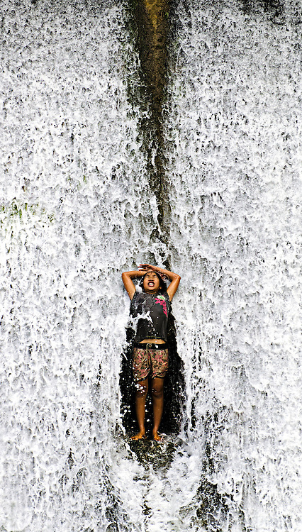 A girl having fun on an overflowing reservoir in Luang Prabang, Laos.