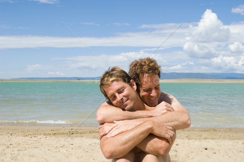 two men with arms wrapped around one another by a lake in New Mexico