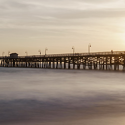 San Clemente pier sunset panorama with the sun setting behind Lifeguard Tower Zero. San Clemente is a popular coastal beach city in Orange County Southern California. Copyright ⓒ 2017 Paul Velgos with All Rights Reserved.