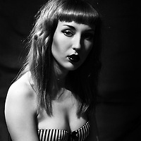 Black and white portrait of a young woman with long hair looking at the camera wearing a striped bra, surrounded by dark interior.